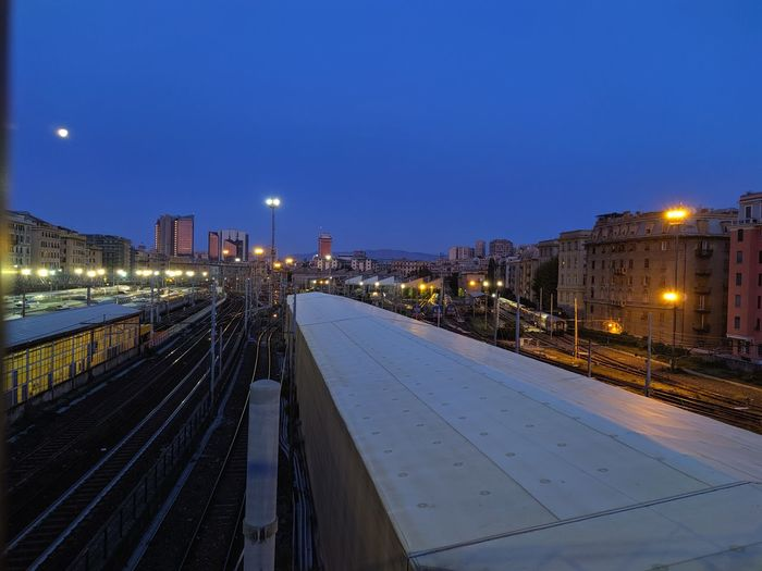 Railroad tracks in city against clear blue sky at night