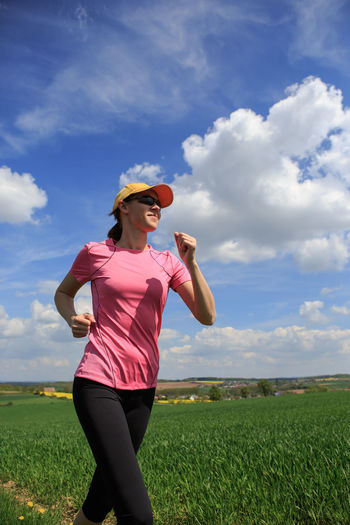 woman jogging through fields at the springtime Action, Activity, Adult, Break, Competition, Drinking, Female, Fields, Fit, Healthy, Jogging, Lifestyles, Nature, Pause, People, Running, Sports, Springtime, Summer, Training, Woman Adult Cloud - Sky Females Field Front View Grass Green Color Land Landscape Leisure Activity Lifestyles Nature One Person Plant Real People Sky Standing Three Quarter Length Women Young Adult