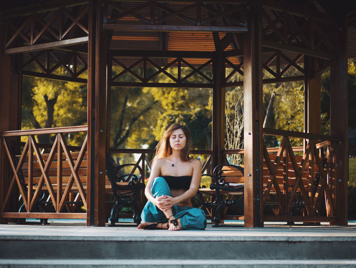 Young woman meditating by gazebo
