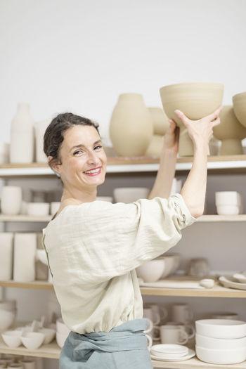 Portrait Of Smiling Mid Adult Potter Holding Ceramics In Workshop