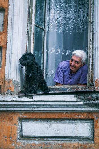 Man with dog sitting by window
