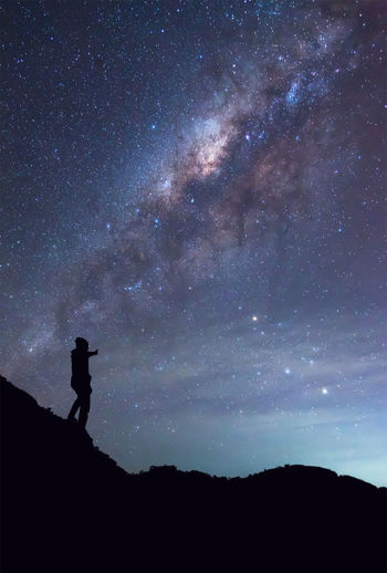 Silhouette mid adult man standing on mountain against star field at night
