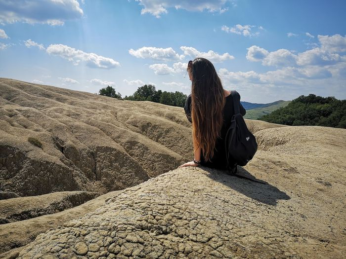 Woman with long hair sitting on rock against sky