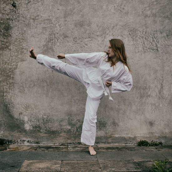 Taekwondo Female Fighter Full Length Girl Kick Leisure Activity Lifestyles Outdoors Self Defense Sport Taek-won-do Taekwon-do Taekwondo White Belt Woman Young Woman