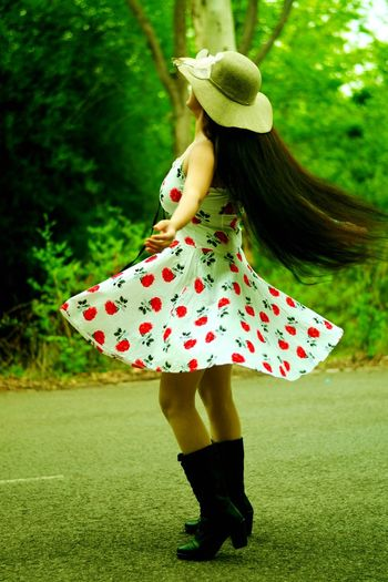 Woman In Dress With Long Hair Walking On Field At Park