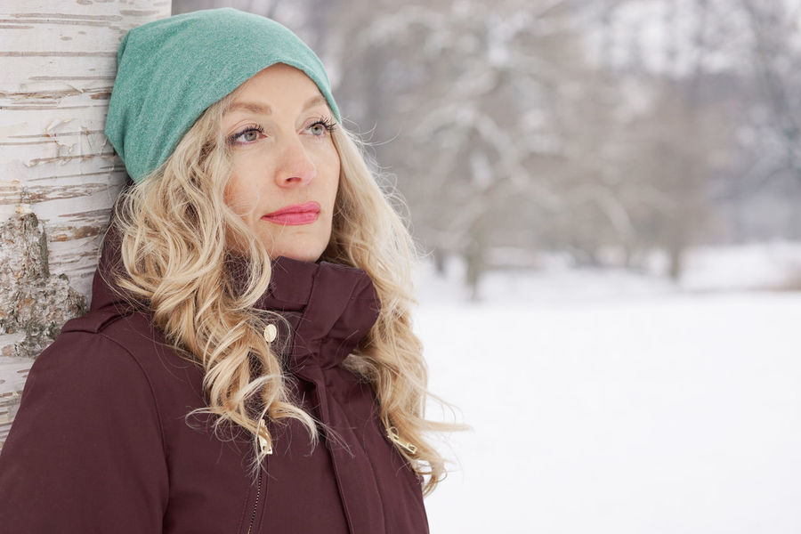 Adult Blonde Cold Temperature Copy Space Day Gazing Into Distance Leaning Against Tree Looking Away Nature One Person Outdoor Park Pensive People Snow Snow Covered Solitude Tree Warm Clothing Winter Woman