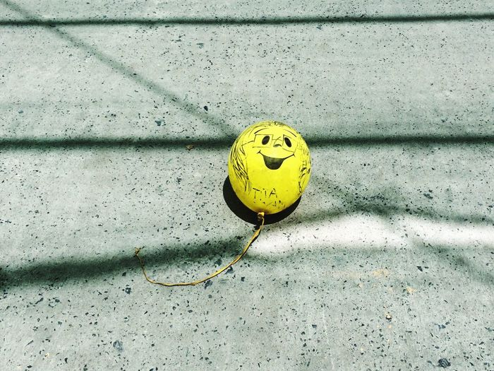Yellow Balloon Face On Concrete Floor