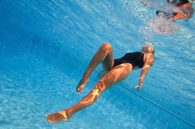 Full length of woman swimming underwater in pool
