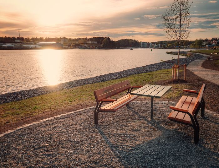 Empty chairs and table by river against sky during sunset