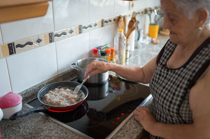Midsection of senior woman preparing food at home