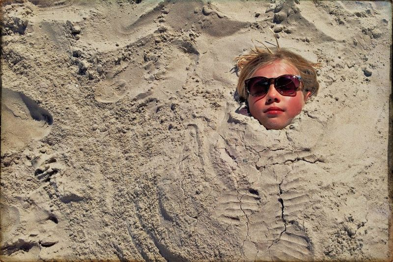 High angle view of teenage girl buried in sand at beach
