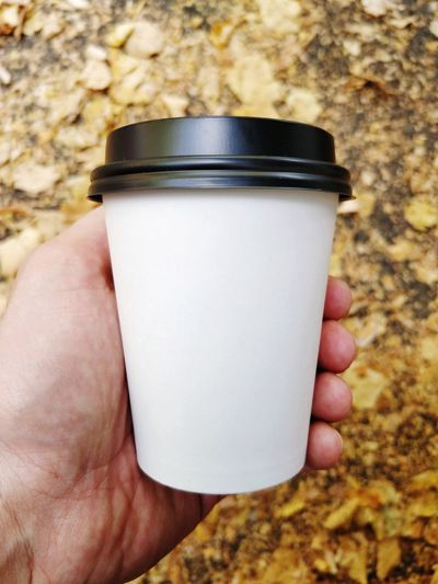 Quick coffee break. Autumn Fall Human Hand Drink Holding Close-up Cappuccino Coffee