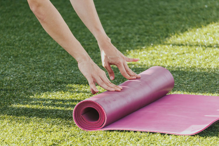 Woman rolling mat after a yoga on green grass Yoga Body Part Day Field Finger Focus On Foreground Grass Green Color Hand Human Body Part Human Hand Land Leisure Activity Lifestyles Low Section Nature One Person Outdoors Plant Real People Women Yoga Practice