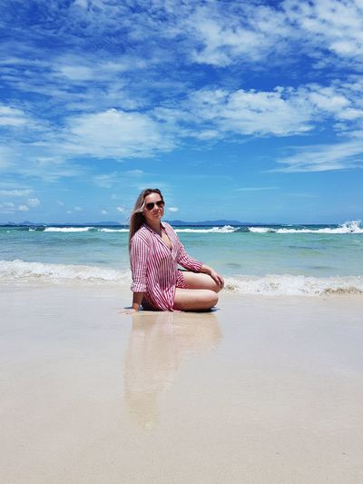 Full Length Of Woman Wearing Sunglasses Sitting At Beach Against Sky