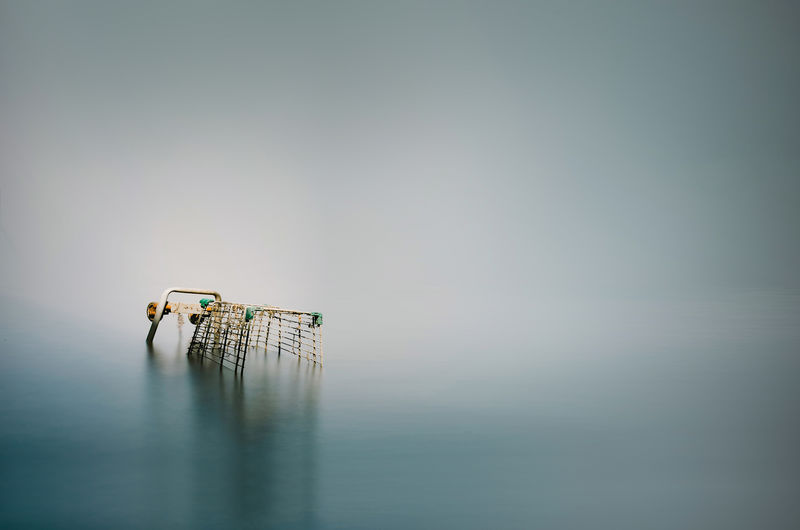 Abandoned shopping cart in sea against sky
