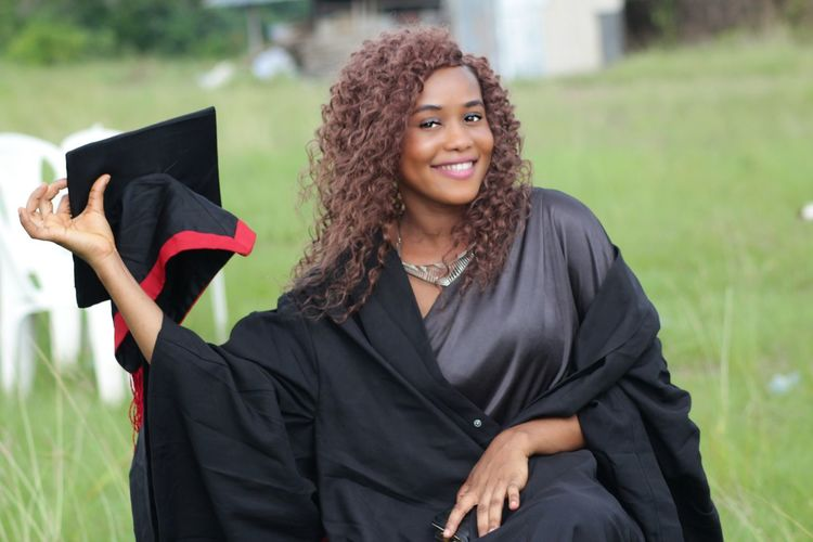 Portrait of smiling woman in graduation gown and mortarboard on field