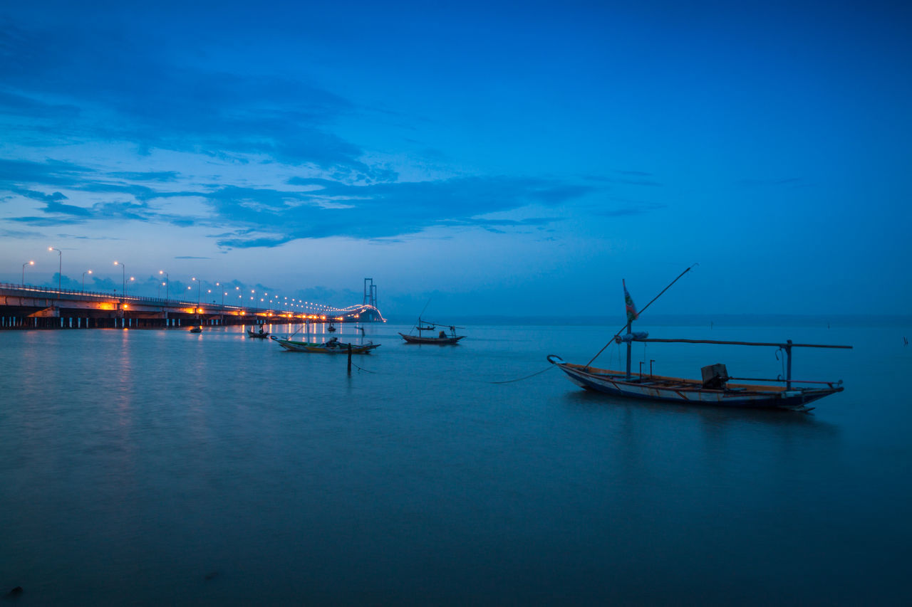 nautical vessel, water, transportation, mode of transport, sea, waterfront, sky, boat, tranquility, blue, nature, dusk, moored, beauty in nature, scenics, outdoors, tranquil scene, sunset, no people, night, harbor, illuminated