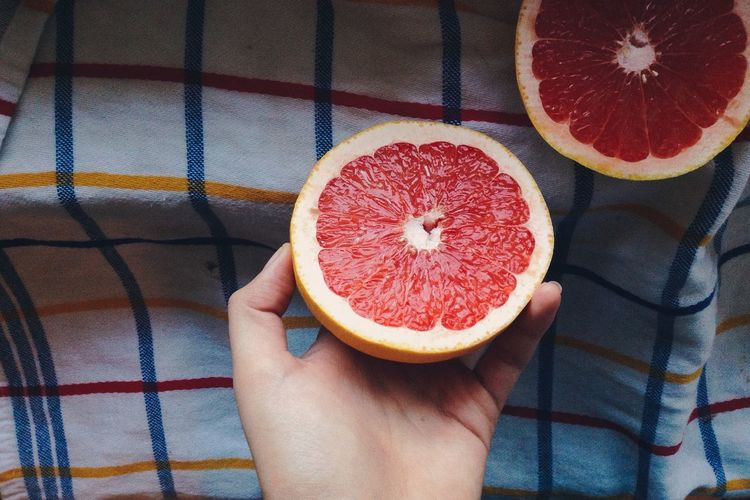 Cropped hand holding grapefruits