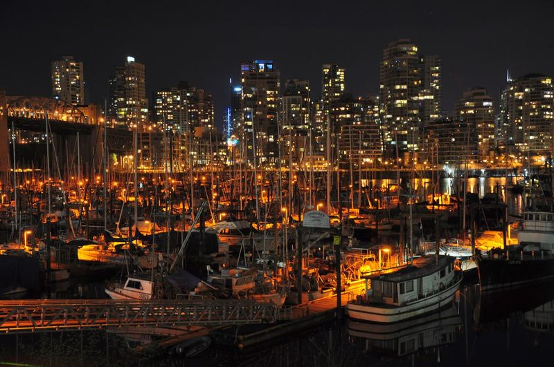Boats Moored At Harbor Against Illuminated Buildings In City At Night