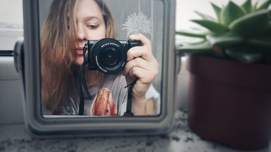 Reflection of woman photographing from camera on mirror