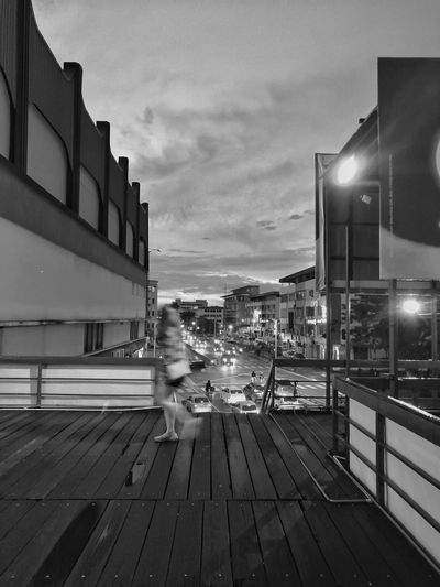 Woman sitting on street against illuminated buildings in city against sky