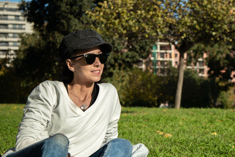 Young man wearing sunglasses sitting on grass
