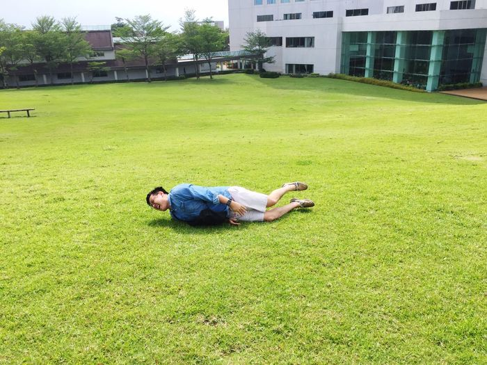 Man lying down on grassy field by lawn against building