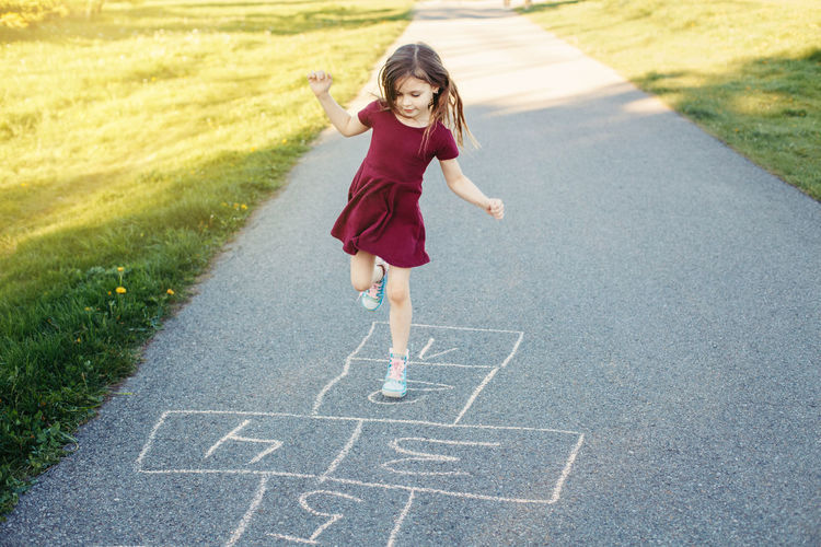 Full length of girl playing on road