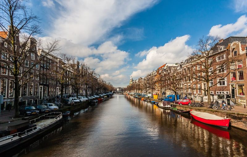 Cloud - Sky Building Exterior Sky Nautical Vessel Architecture Mode Of Transport Built Structure Moored Canal Transportation Water Day Outdoors Travel Destinations Waterfront No People Harbor Bare Tree Nature Tree Amsterdam Netherlands Holland