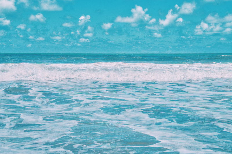 Waves rushing towards beach against cloudy sky
