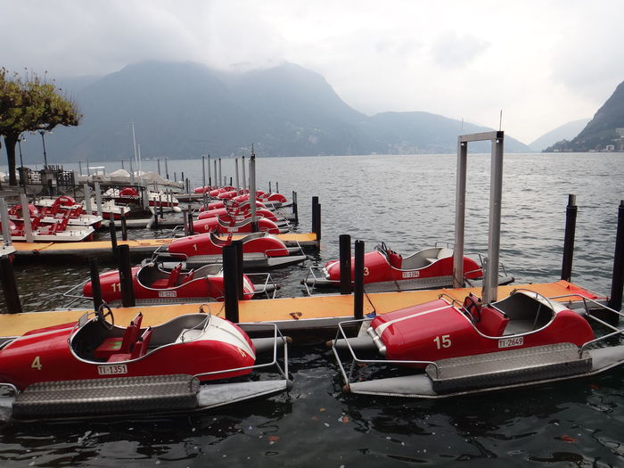 Side View Of Boats Moored In Lake