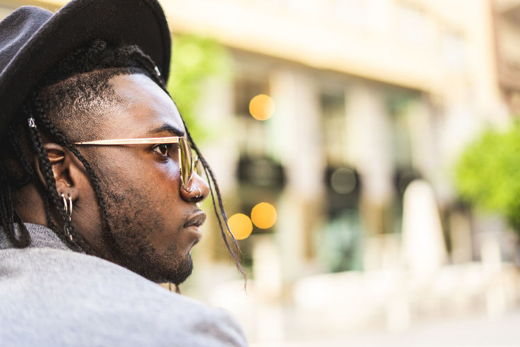 Portrait of young man looking away in city