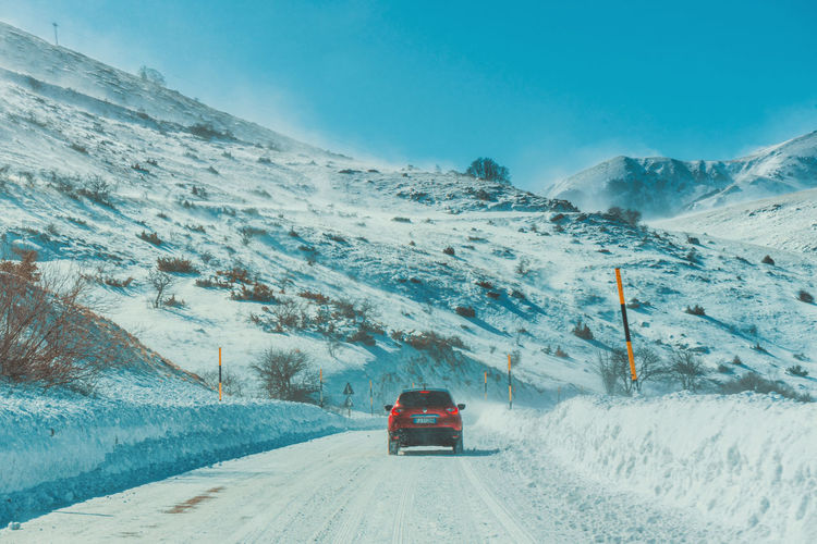 People on snow covered mountain road against sky