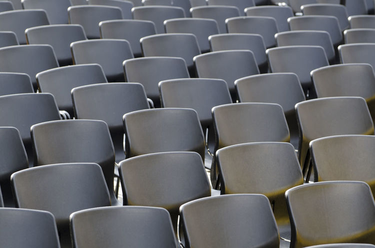 Black chairs in a row Abbundance, Auditorium Black Color Chair Chairs Day Diminishing Perspective Empty Chair Empty Chairs Full Frame In A Row Many No People Objects Outdoors Pattern Repetition Seat Side View Stadium Sunny Tranquility