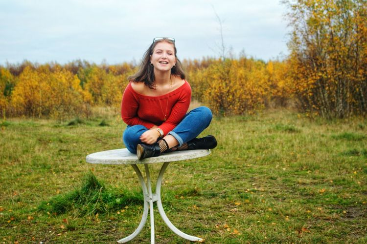 Portrait of young woman sitting on table against sky