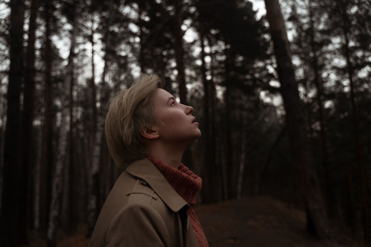Profile view of woman standing against trees in forest