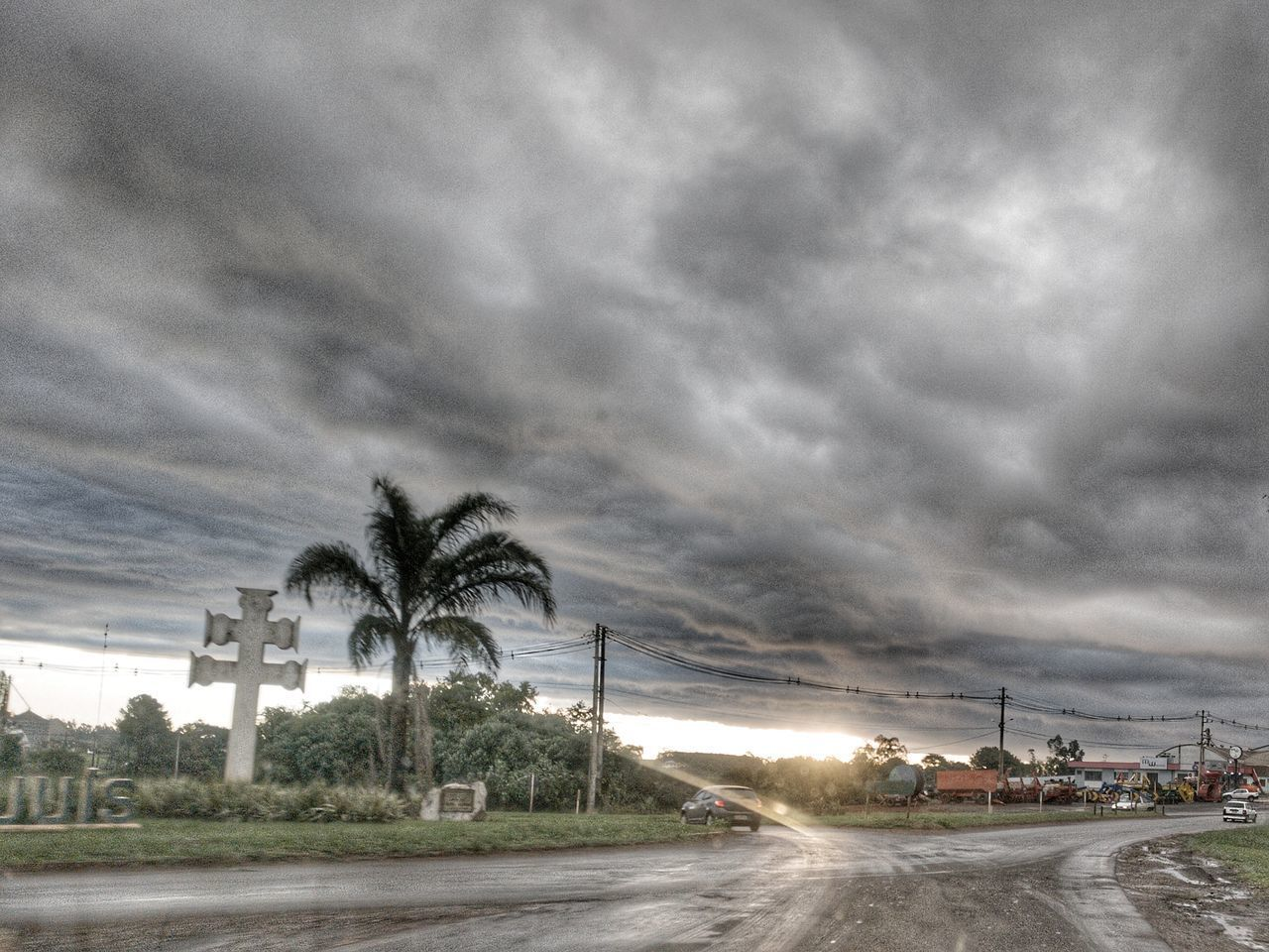 palm tree, cloud - sky, sky, tree, storm cloud, road, weather, outdoors, street light, transportation, nature, built structure, no people, architecture, building exterior, illuminated, city, beauty in nature, day, water, thunderstorm