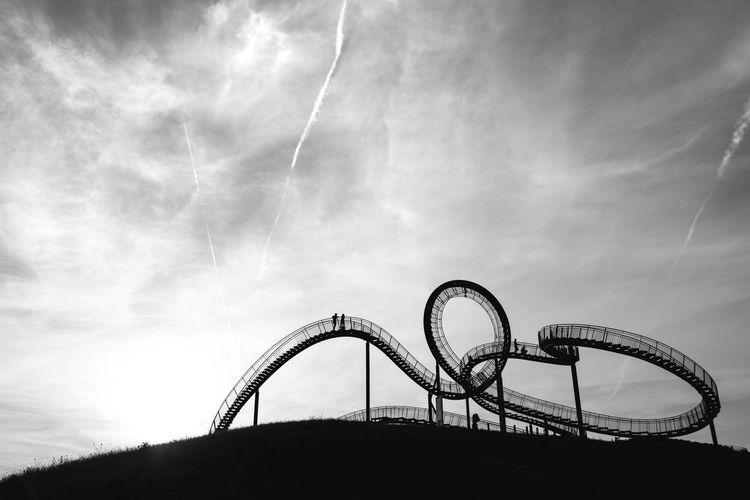 Rollercoaster Against Cloudy Sky At Amusement Park