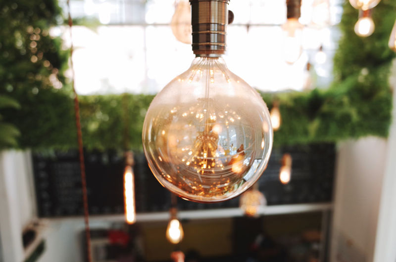 Focus On Foreground Lighting Equipment Glass - Material Illuminated Transparent Light Bulb Close-up Filament Hanging Electricity  Incidental People Electric Light Indoors  Decoration Sphere Light Day Reflection
