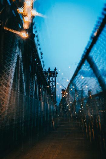 Illuminated bridge against clear blue sky at dusk