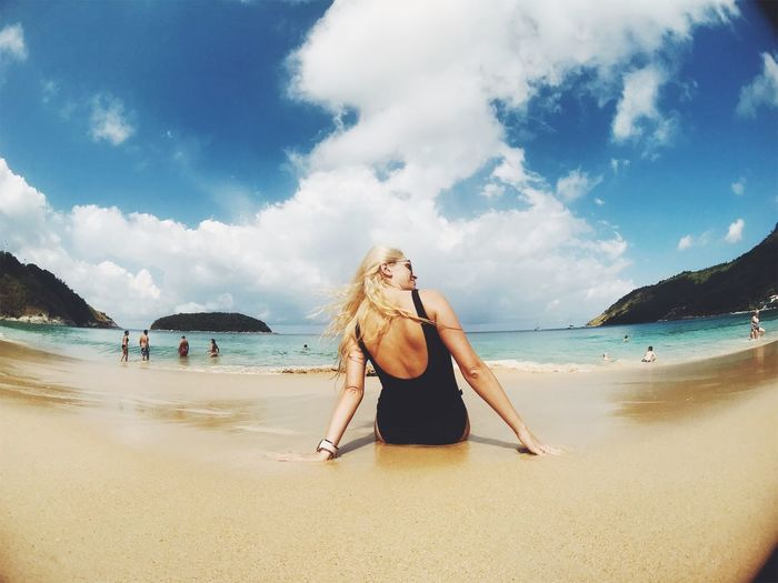 Rear view of woman sitting at beach against cloudy sky