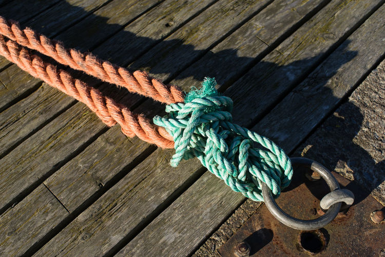 mooring Blue Close-up Day Deck Dock Green Color High Angle View Knot No People Outdoors Rope Sunlight Textured  Wood - Material Wood Paneling