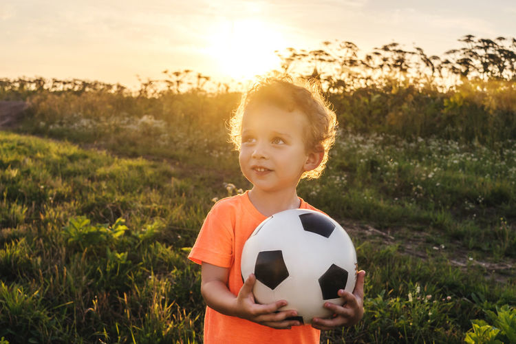 Cute boy holding ball while standing on grassy land at sunset