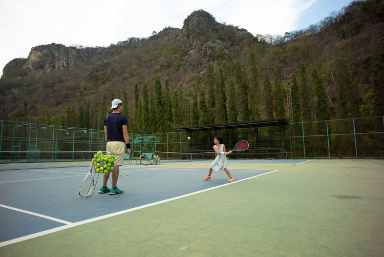 Portrait Asian girl plays tennis with her father and coach at outdoor court with stone mountain and forest background Sport Full Length Real People Men Plant Leisure Activity Lifestyles Day Nature Tree Casual Clothing People Playing Males  Women Outdoors Mountain Landscape Tennis Court Racket Hanging Out Backhand Active Movement Training Coach Practice Basic Young Adult Cute Concentration Focus Backgrounds