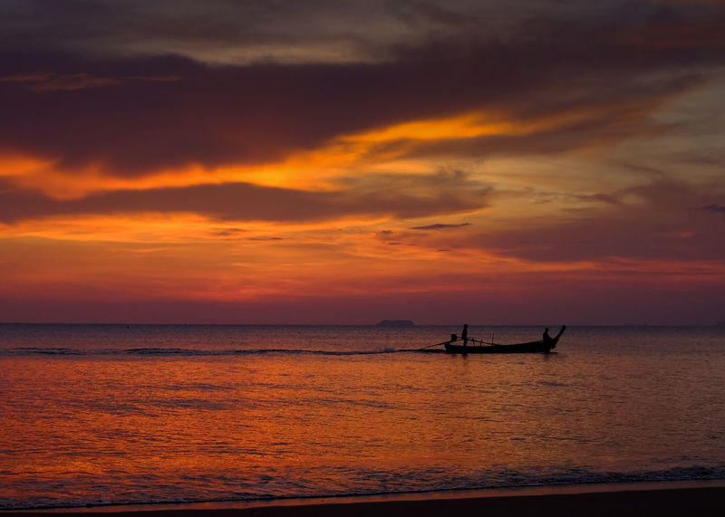 Thai longtail fishing boat moving across sea near the shore, under a dramatic sunset. Boat Coming Home Dramatic Sky Fishing Boat Longtailboat Ocean Orange Sky Peace Sea Serenity Sunset Thailand Tranquility 43 Golden Moments Colour Of Life Lost In The Landscape