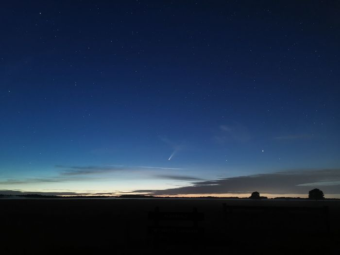 Silhouette landscape against blue sky at night