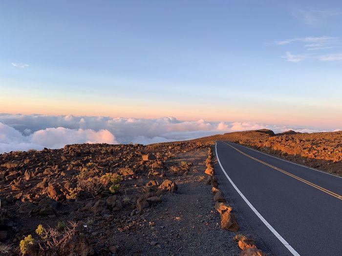 Road leading towards landscape against sky during sunset