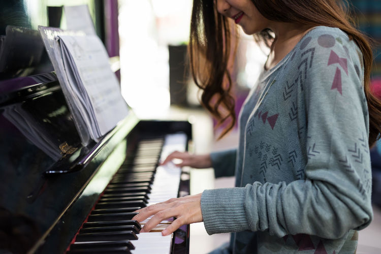 Midsection of woman playing piano