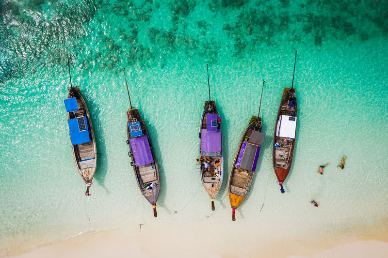 High angle view of longtail boats moored at shore of beach