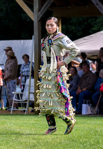 september 3, 2017, an American Indian girl in a jingle dress dances during a competition at the Kee-Boon-Mein-Kaa Pow Wow in Dowagiac Michigan USA Beautiful Dancing Michigan, USA Performer  Pow Wow Spectators Traditional Clothing Adult Amerircan Indian Bells Clothing Competition Editorial Photography Females Full Length Hand Made Jingle Dress Musical Native American Nature Outdoors Real People Regalia Vertical Women